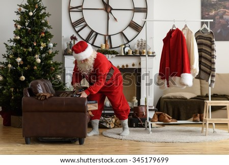 Santa Claus at Home Packing his Clothes, Preparing for Travel - stock photo