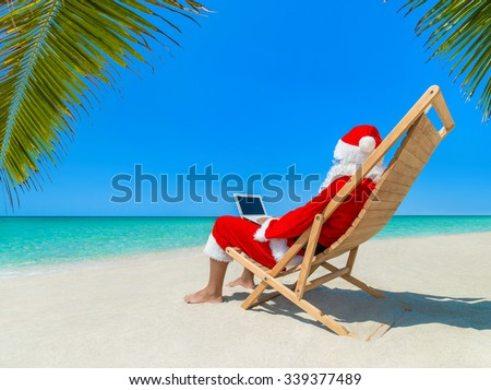 Santa Claus at tropical ocean beach in wooden deckchair work using laptop computer - Christmas orders for gifts from children concept
