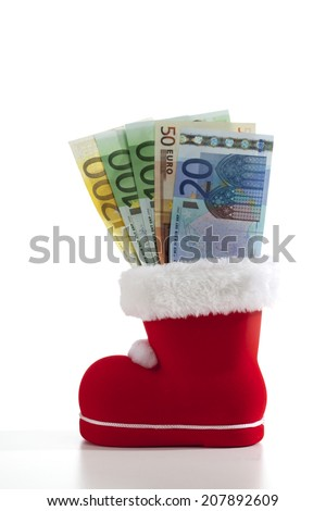 Santa Claus boot filled with euro notes on white background - stock photo