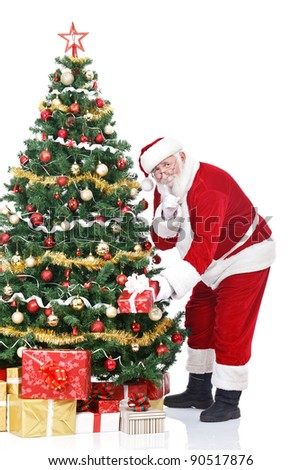 Santa Claus bringing gifts and putting under Christmas tree, isolated on white background - stock photo