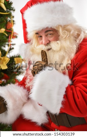 Santa Claus bringing gifts and putting under Christmas tree with silence gesture
