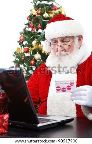 Santa Claus buying on-line using credit card, isolated on white background - stock photo