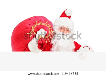 Santa Claus carrying a bag and posing behind a blank billboard isolated on white background