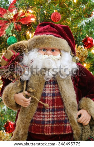 Santa Claus carrying a sack bag full of presents with blurred Christmas tree background