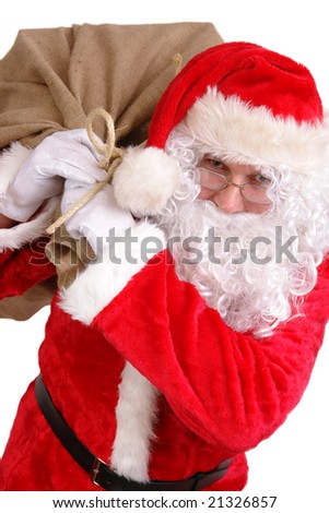 Santa Claus carrying big sack on his shoulder full of christmas presents