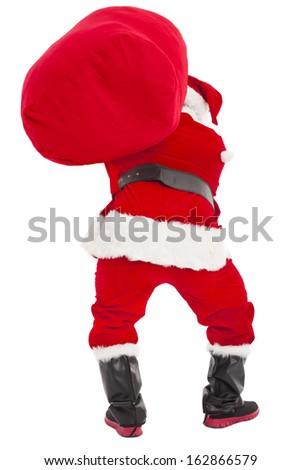 santa claus carrying heavy gift bag - stock photo