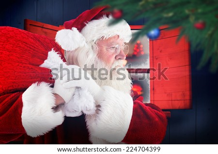 Santa claus carrying sack against christmas at home