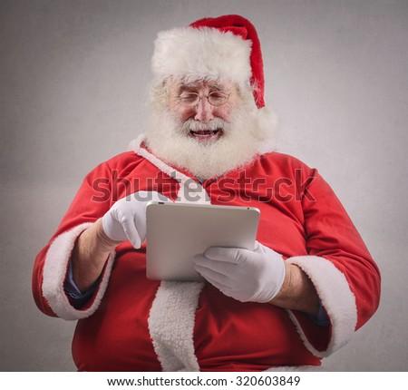 Santa Claus checking his tablet - stock photo