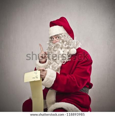 Santa Claus checking the gift list - stock photo