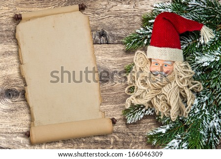 Santa Claus christmas decoration with pine tree branch and vintage scroll paper over rustic wooden background with place for your text - stock photo