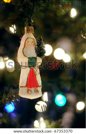 Santa Claus Christmas Ornament hanging on a Christmas Tree with lights. Copyspace with room for your text. - stock photo