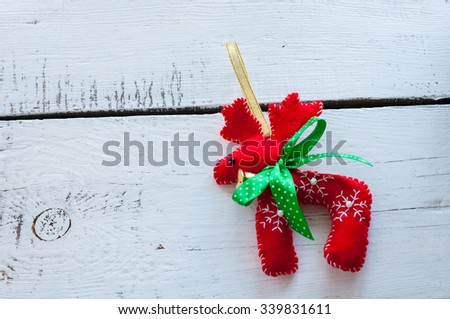 Santa Claus Christmas reindeer - red toy with green bow, on white wooden background with empty space for text. - stock photo
