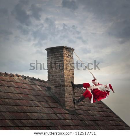 Santa Claus climbing a roof