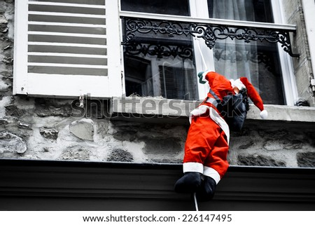 Santa Claus climbing up a wall into a window. Traditional Christmas decoration. Aged photo. - stock photo