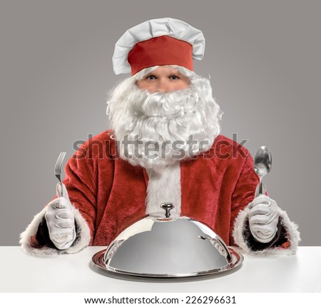 Santa Claus cook chef with fork, spoon and food tray on isolated background - stock photo
