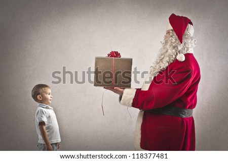 Santa Claus delivering a gift to a child - stock photo