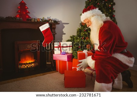 Santa claus delivering gifts at christmas eve at home in the living room