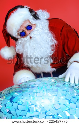 Santa Claus DJ near brilliant sparkling disco ball. Christmas celebration. - stock photo