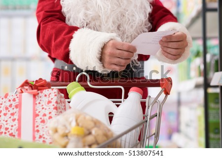 Santa Claus doing grocery shopping at the supermarket, he is pushing a full cart and checking a list, Christmas and shopping concept
