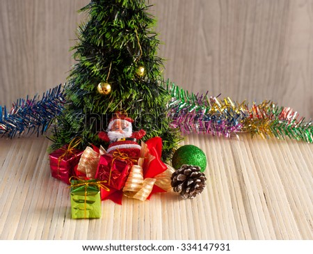 Santa Claus doll against a Christmas tree with gift box on wood background - stock photo