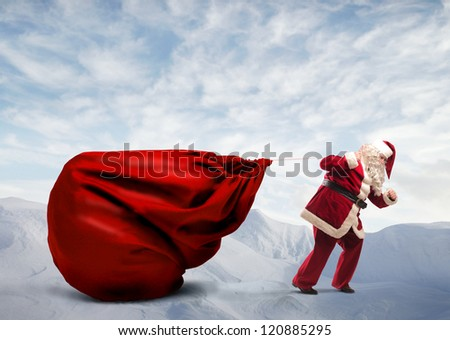 Santa Claus dragging his very large full of presents on a mountain - stock photo