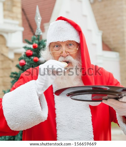 Santa Claus eating cookie against house - stock photo