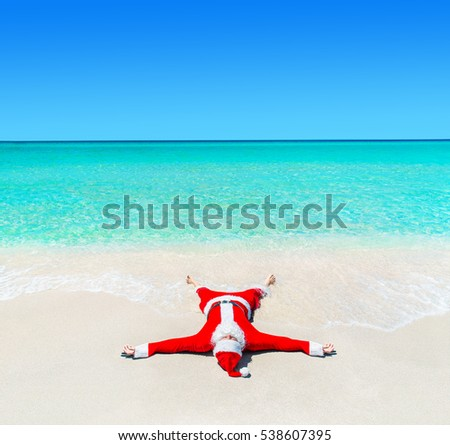 Santa Claus enjoy tanning at tropical ocean beach in turquoise water waves, Christmas and New Year vacation destinations in hot countries concept