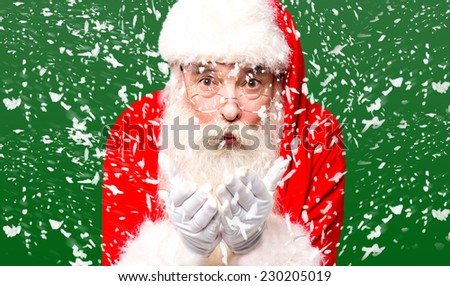 Santa claus enjoying winter by blowing snow - stock photo