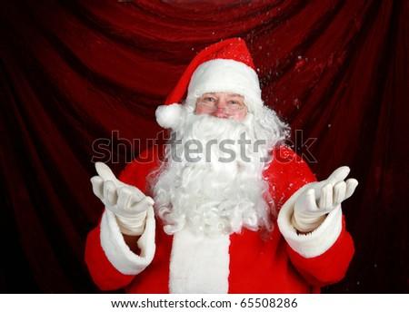Santa Claus enjoys fresh falling snow while he prepares for the Christmas Rush - stock photo