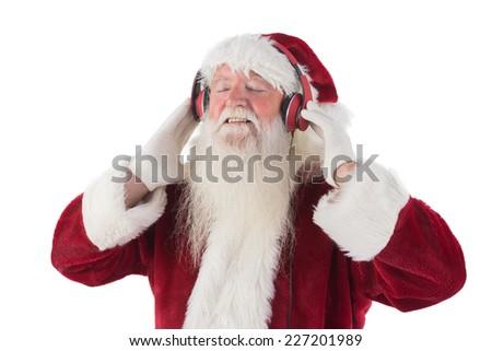 Santa Claus enjoys some music on white background - stock photo
