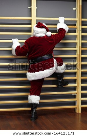santa claus exercising with wall bars,Christmas Time preparation - stock photo