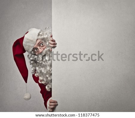 Santa Claus faces leaning against a wall - stock photo