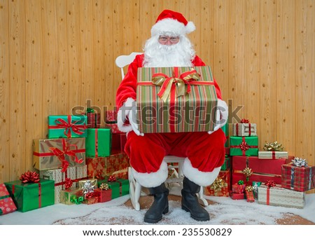 Santa Claus / Father Christmas sitting in his grotto holding a gift wrapped present for you. - stock photo