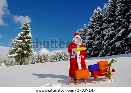 Santa Claus, Father Christmas with colorful presents on a sledge - stock photo
