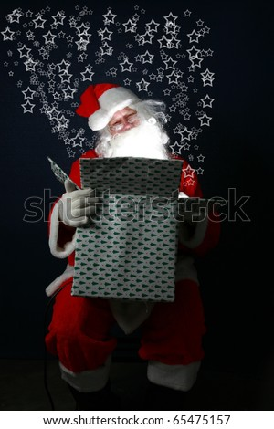 "Santa Claus fills a Christmas Present with ""Christmas Magic"" and love for everyone around the world. The bright light of Christmas Magic lights up santa's face from inside the box - stock photo"