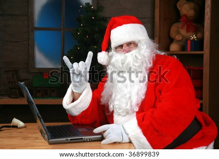 "Santa Claus flashes the ""devil horns"" sign also known as ""Hook 'em 'horns"" and  ""mano cornuto"" while checking his e mail - stock photo"