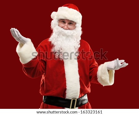 Santa Claus gesturing his hand isolated over red background. Presenting something - stock photo