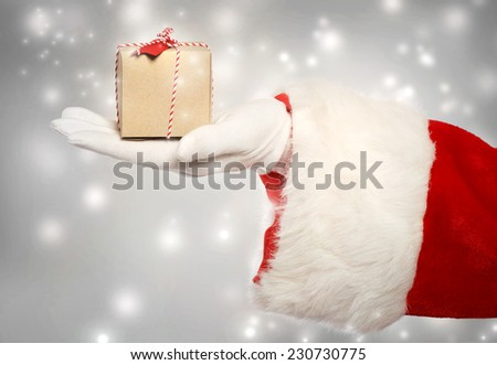 Santa claus giving a small christmas present box in snowy night  - stock photo