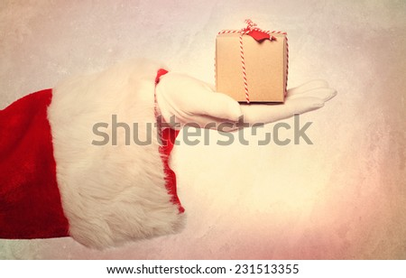 Santa Claus giving a small Christmas present box in vintage style - stock photo