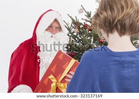 Santa Claus giving gift to Boy - stock photo