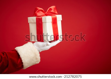 Santa Claus gloved hand with giftbox in isolation - stock photo