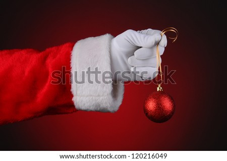 Santa Claus hand holding a sparkly red ornament on a gold ribbon over a light to dark red background. Horizontal format hand and arm only. - stock photo