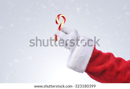 Santa Claus hand holding an old fashioned candy cane. Over a snowy background, hand and arm only with copy space. - stock photo