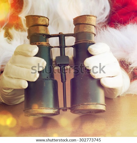 Santa Claus hand holding binocular - stock photo
