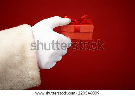 Santa Claus hand in white glove holding small red giftbox - stock photo