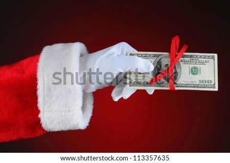 Santa Claus hand with cash tied up with a red ribbon. Horizontal format over a light to dark red background. - stock photo
