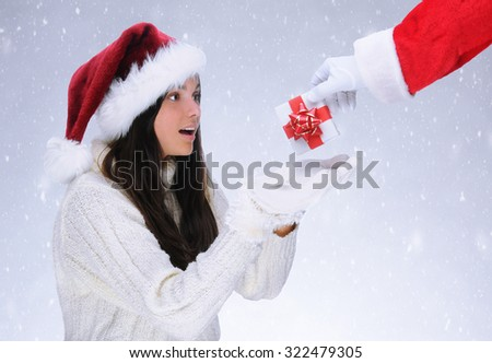 Santa Claus handing a Christmas present to a teenage girl with a surprised look on her face. Horizontal format with a snowy background.