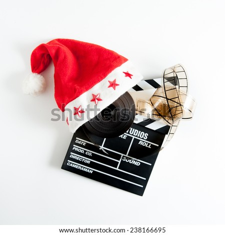 Santa Claus hat on a movie clapper board and a film reel isolated on white background - stock photo