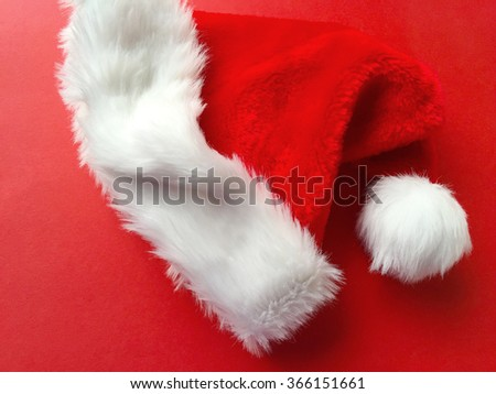 Santa Claus hat on red background - stock photo