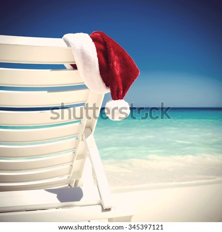 Santa Claus Hat on sunbed near  tropical calm beach with turquoise caribbean sea water and white sand. Christmas vacation concept - stock photo
